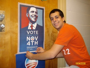 Danny pauses for a photo while attaching a poster to a fellow Obama supporter's door.