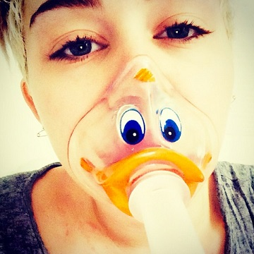 Miley Cyrus with a duck-face oxygen mask while in the hospital (photo from www.eonline.com)