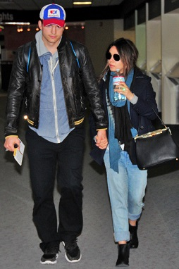 Mila Kunis, with her layered baby bump, and Ashton Kutcher travel through an Iowa airport to visit his family