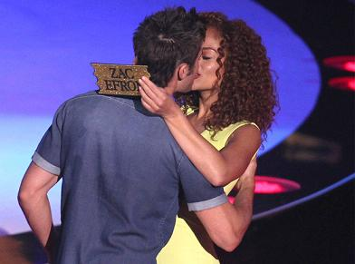 Zac Efron kissing this mystery woman from the audience while she flashes her lucky golden ticket (photo from www.eonline.com)