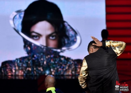 Usher performing to Michael Jackson's newest song as the King of Pop's album art is displayed (photo from http://news.iheart.com/awards/)