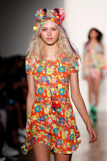 A model walking in Fashion Week wearing Jeremy Scott's clothing and Miley Cyrus's accessories.
