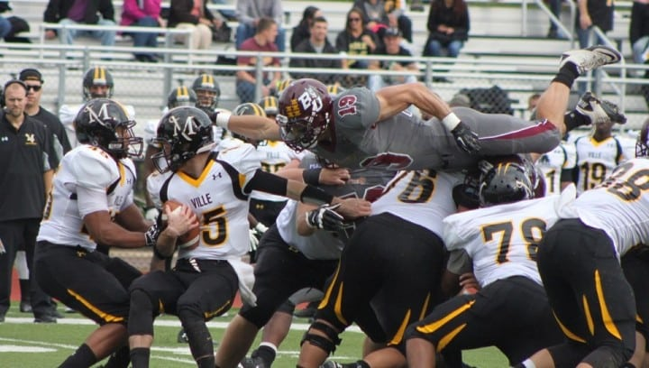 Safety Eric Schwartz (19) leaps over the Millersville offensive line for one of his five tackles. The redshirt sophomore also had a forced fumble on the afternoon.
