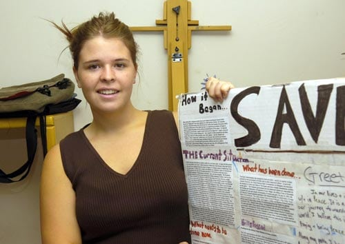 Kayla Mueller Displays a Poster Explaining the Situation in Darfur