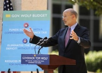 Gov. Tom Wolf speaks in front of the Bellefonte Area High School on Monday, July 13, 2015 in Bellefonte, Pa. Wolf was outside the capital Monday, touting his budget agenda at schools in Bellefonte and Pittsburgh. No negotiations between the Wolf administration and leaders of the Legislature's Republican majority are scheduled as Pennsylvania's budget stalemate approaches its third week. (Nabil K. Mark/Centre Daily Times via AP) MANDATORY CREDIT; MAGS OUT