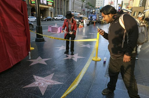 A man takes a photo of the vandalized star for Republican presidential candidate Donald Trump on the Hollywood Walk of Fame, Wednesday, Oct. 26, 2016, in Los Angeles. Det. Meghan Aguilar said investigators were called to the scene before dawn Wednesday following reports that Trump's star was destroyed by blows from a hammer. (AP Photo/Richard Vogel)