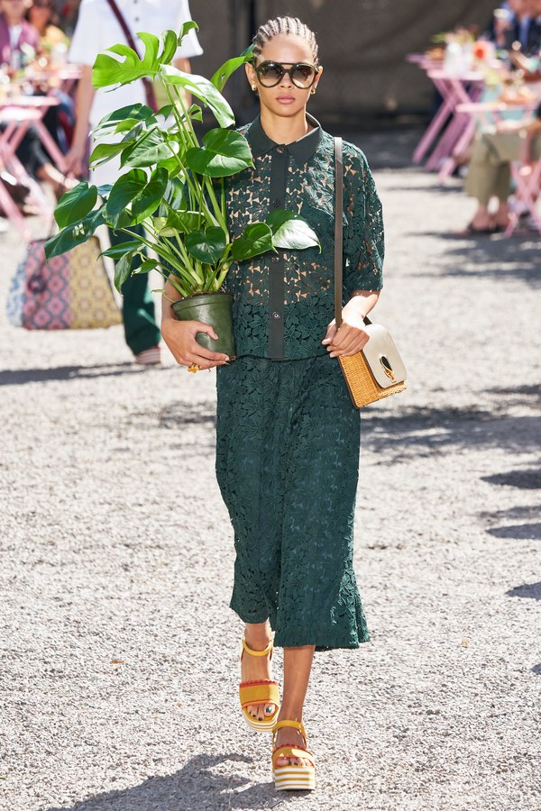 Model walks the runway holding a plant.